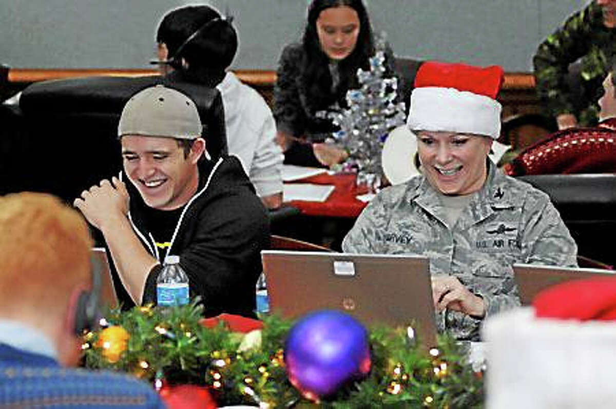 Volunteer tracker Matthew Harvey joined his mother Col. Tina Harvey to help answer emails from children and parents across the globe while at the NORAD Tracks Santa Operations Center on Peterson Air Force Base, Colorado Dec. 24, 2014. Photo by Air Force Master Sgt. Chuck Marsh