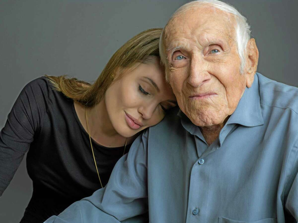 """This undated photo provided by Universal Pictures shows Angelina Jolie with Louis Zamperini. Zamperini, a U.S. Olympic distance runner and World War II veteran who survived 47 days on a raft in the Pacific after his bomber crashed, then endured two years in Japanese prison camps, died Wednesday, according to Universal Pictures studio spokesman Michael Moses. He was 97. Jolie is directing the Universal movie, """"Unbroken,"""" about the life of Zamperini."""