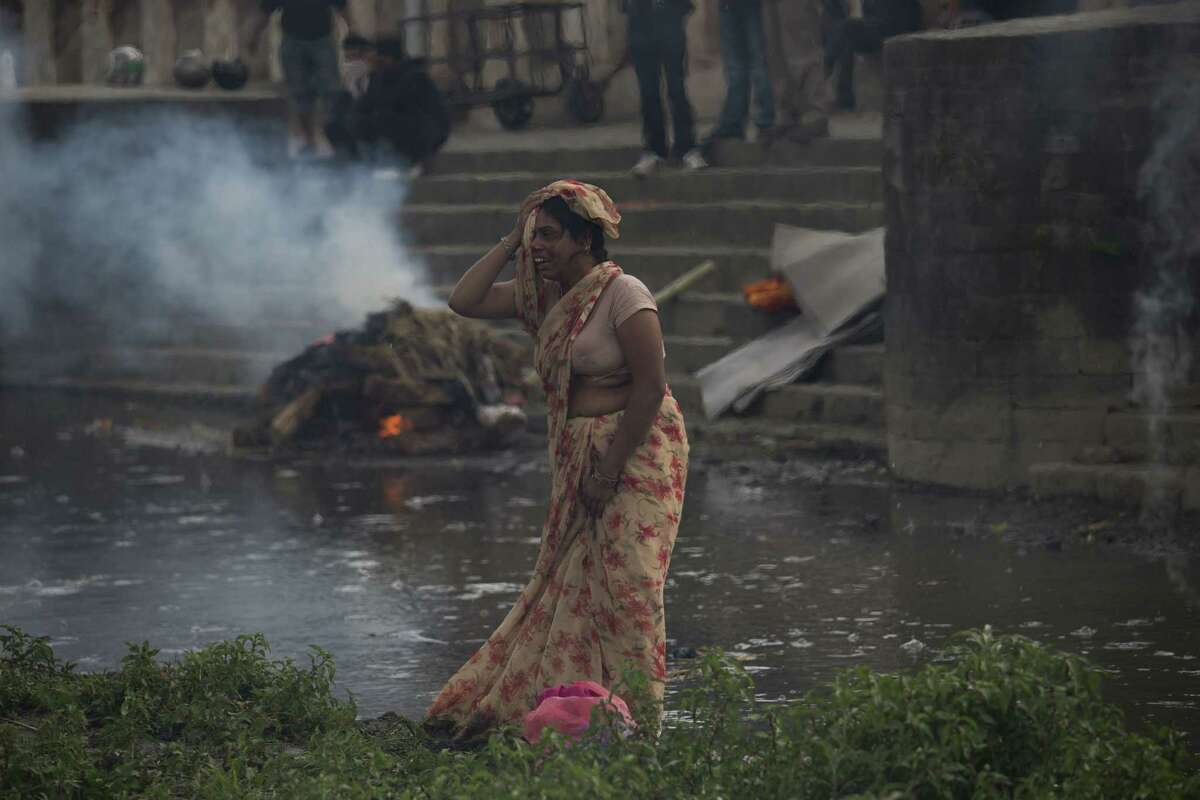 A woman weeps during the cremation of an earthquake victim at the Pashupatinath temple, on the banks of Bagmati river, in Kathmandu, Nepal on April 26, 2015.