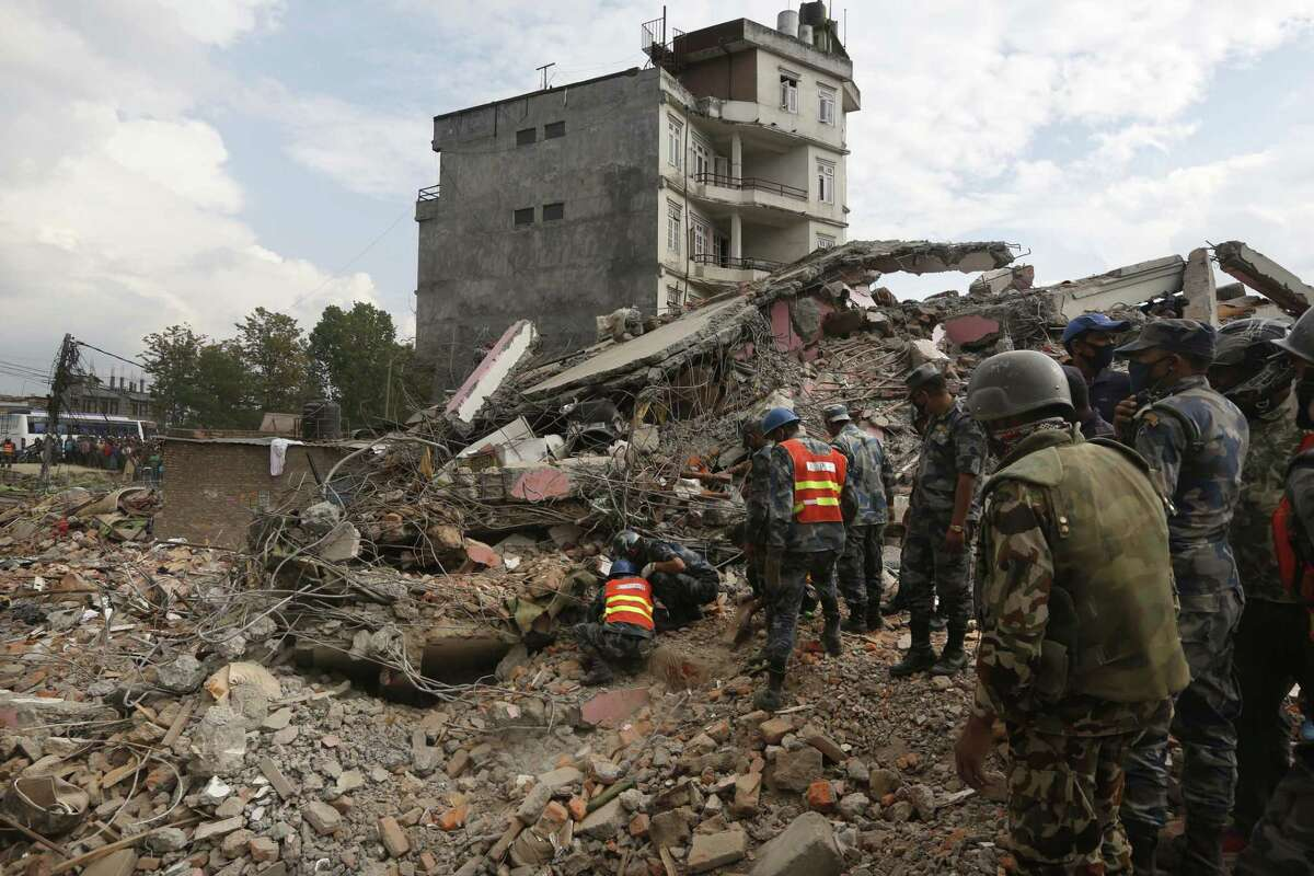 Nepalese policemen look for survivors in the debris of a building that collapsed in an earthquake in Kathmandu, Nepal, on April 26, 2015.