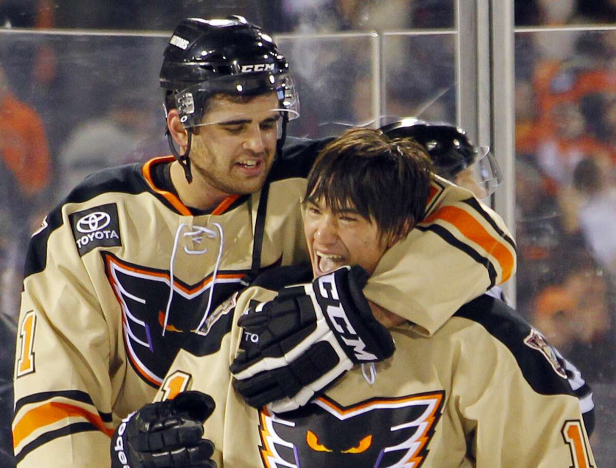 The Adirondack Phantoms' Tom Sestito, rear, wraps his arm around teammate Shane Harper who scored the winning goal during overtime of an AHL hockey game against the Hershey Bears in Philadelphia. The new overtime rule implemented in the AHL this season is a roaring success and could soon be seen at an NHL rink near you.