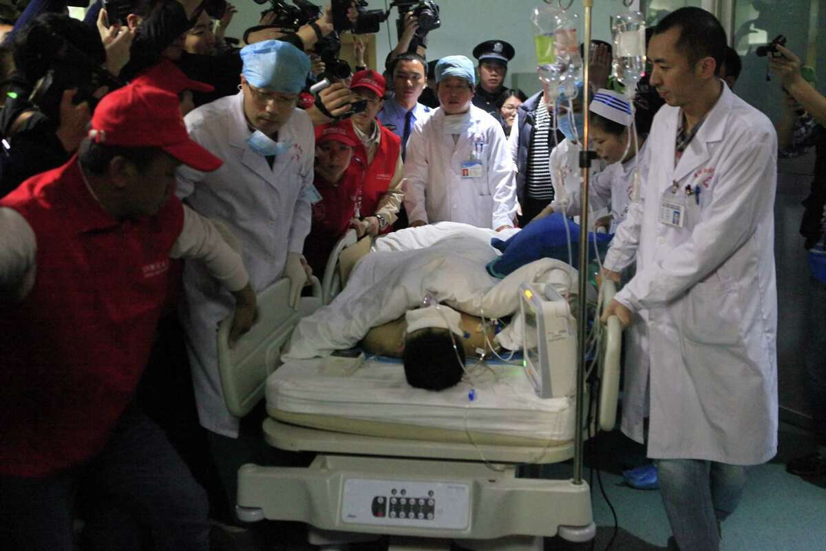 Medical staff move landslide survivor Tian Zeming following surgery in a hospital in Shenzhen in southern China's Guangdong province Wednesday, Dec. 23, 2015. Rescuers pulled Tian from the rubble of a massive landslide in Shenzhen early on Wednesday, 67 hours after he had been buried.