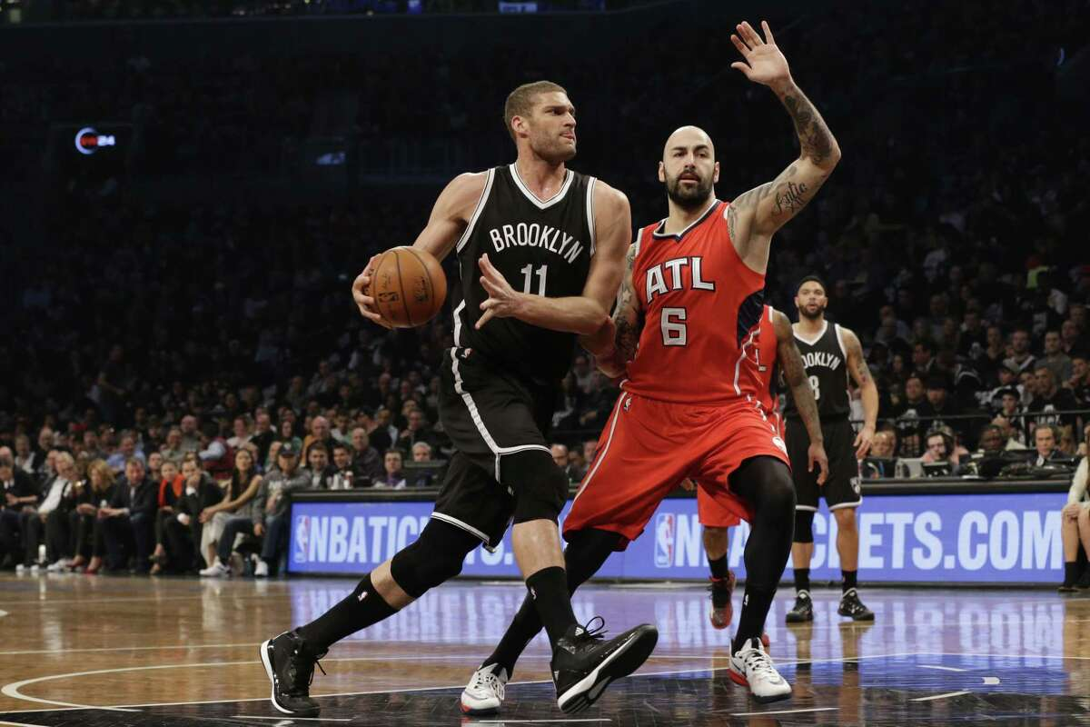 Brooklyn Nets center Brook Lopez drives to the basket against Atlanta Hawks forward Pero Antic during Game 3 Saturday in New York.