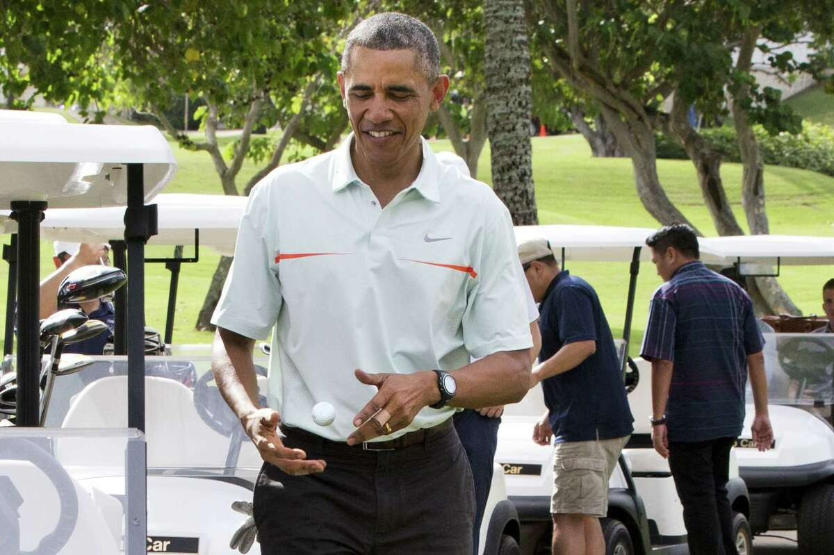Surrounded by Secret Service Agents, President Barack Obama tosses a golf ball between his hands after finishing the 18th hole of a game of golf with Malaysian Prime Minister Najib Razak on Dec. 24, 2014, at Marine Corps Base Hawaii's Kaneohe Klipper Golf Course in Kaneohe, Hawaii during the Obama family vacation.
