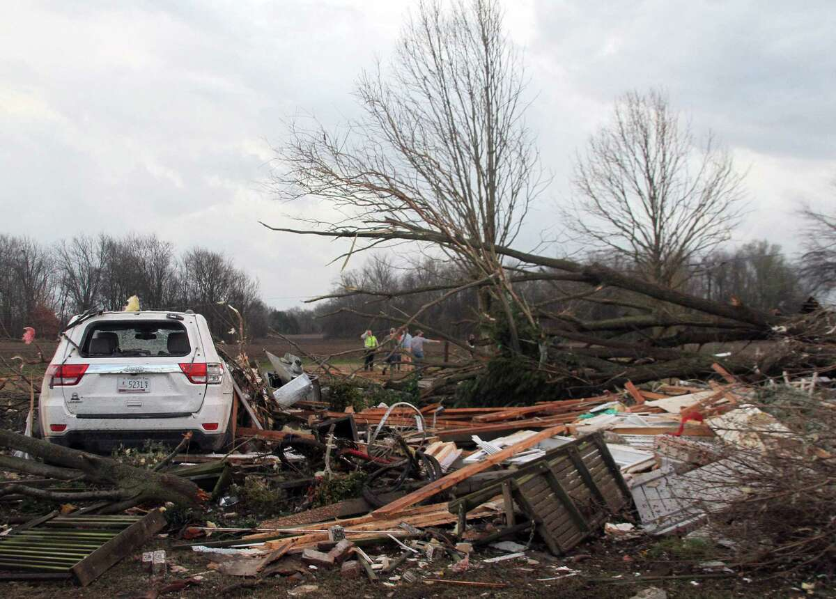 """Neighbors inspect the remains of a storm-damaged home in the Roundaway community near Clarksdale, Miss., Wednesday, Dec. 23, 2015. A storm system forecasters called """"particularly dangerous"""" killed multiple people as it swept across the country Wednesday."""