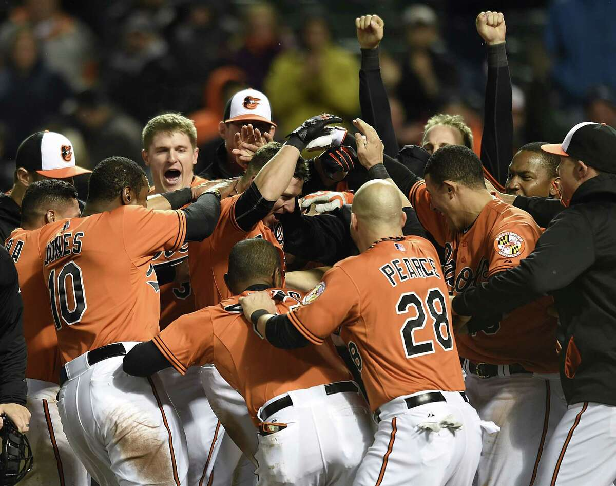 The Orioles' David Lough, center, is surrounded by teammates after hitting a walk-off home run against the Boston Red Sox in the 10th inning Saturday night in Baltimore.