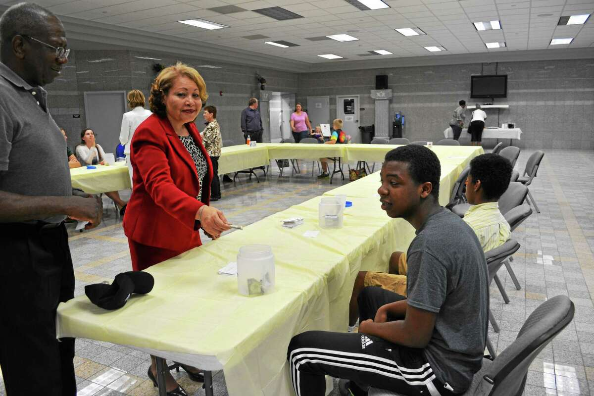 Brian Zahn — The Middletown Press Rosa Browne, president of the Middlesex County branch of the NAACP, puts a dollar in the jar in front of student Kuron Johnson after he correctly defines a vocabulary word.