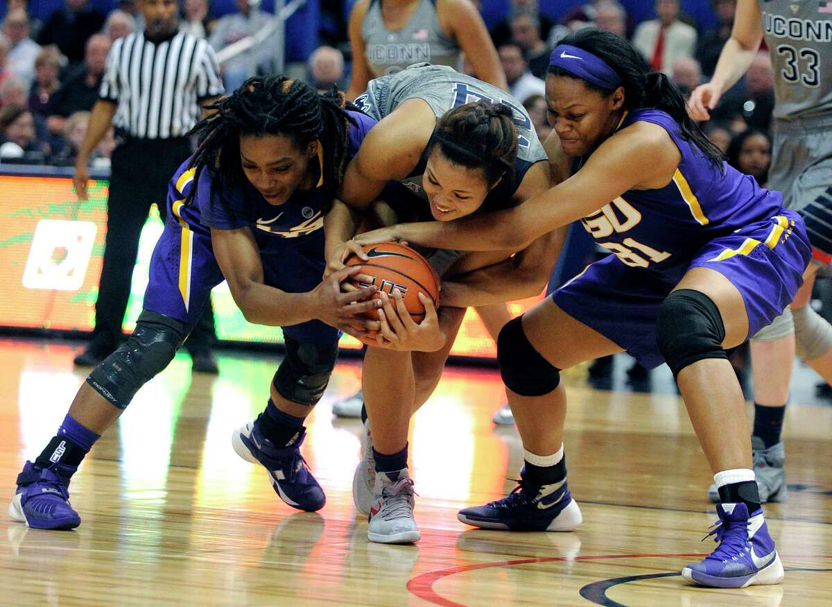 LSU's Jasmine Rhodes, left, and Ann Jones, right fight for a loose ball with Connecticut's Napheesa Collier (24) during the first half on Monday.