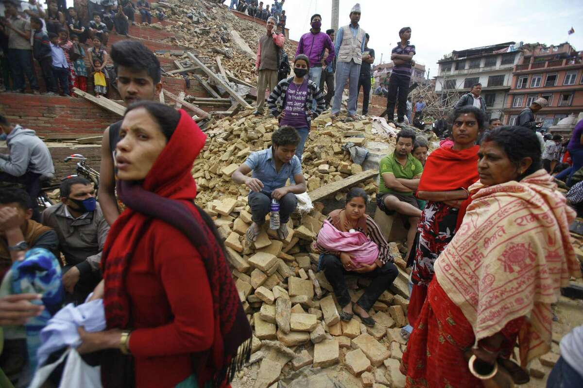 People rest on debris at Durbar Square after an earthquake in Kathmandu, Nepal, Saturday, April 25, 2015. A strong magnitude-7.9 earthquake shook Nepal's capital and the densely populated Kathmandu Valley before noon Saturday, causing extensive damage with toppled walls and collapsed buildings, officials said. (AP Photo/ Niranjan Shrestha)
