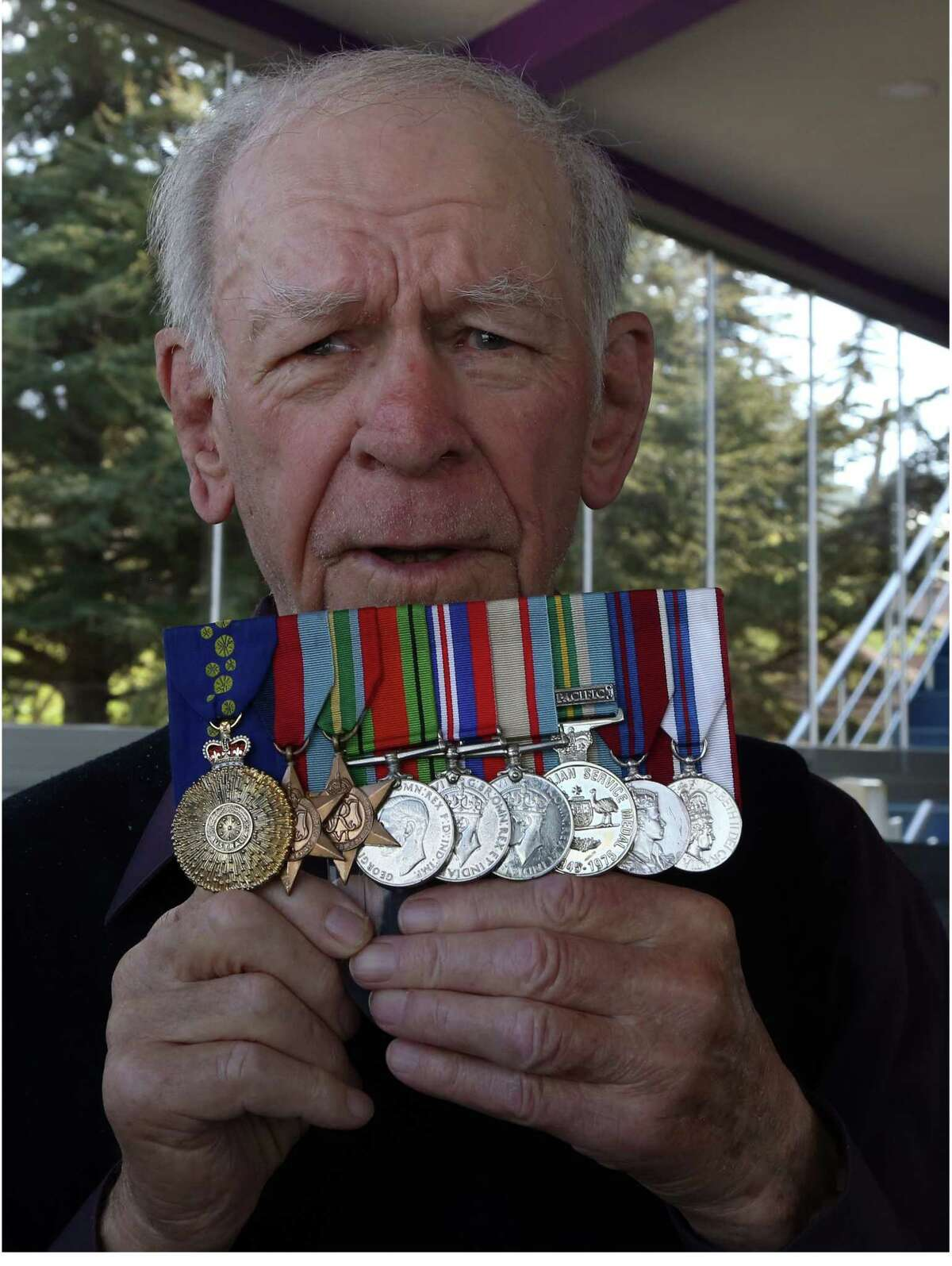 In this image taken Friday, April 24, 2015 Bill Grayden shows his medals as he speaks to The Associated Press in Gallipoli, Turkey, Friday. For the first time at age 95, Grayden has come to Gallipoli, where his father stormed the beach and took a bullet through his lung during the ill-fated British-led World War I invasion. Grayden was among thousands of Australians and New Zealanders who made the pilgrimage from the southern hemisphere to this distant peninsula in Turkey.(AP Photo/Burhan Ozbilici)