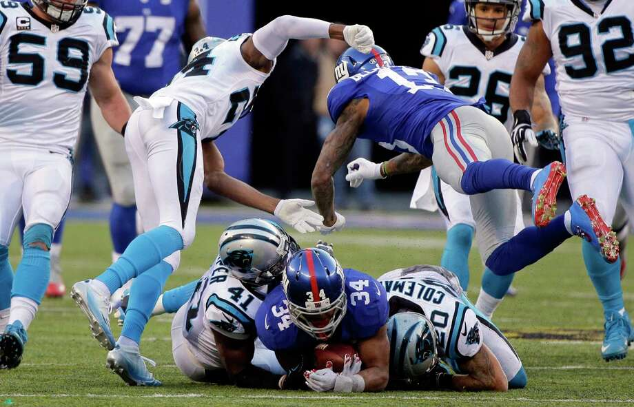 FILE - In this Dec. 20, 2015, file photo, New York Giants' Odell Beckham (13) hits Carolina Panthers' Josh Norman (24) after teammate Shane Vereen (34) was tackled by Kurt Coleman (20) and Roman Harper (41) during the second half of an NFL football game Sunday, Dec. 20, 2015, in East Rutherford, N.J. Beckham, involved in a game-long helmet-smacking, shoving and jawing session with Norman, scored the tying touchdown with 1:46 left in the Giants' 38-35 loss to Carolina. The question for the NFL is why was OBJ still in the game after losing his cool so many times as Norman was getting the best of him in their high-profile matchup. (AP Photo/Julie Jacobson, File) Photo: AP / AP