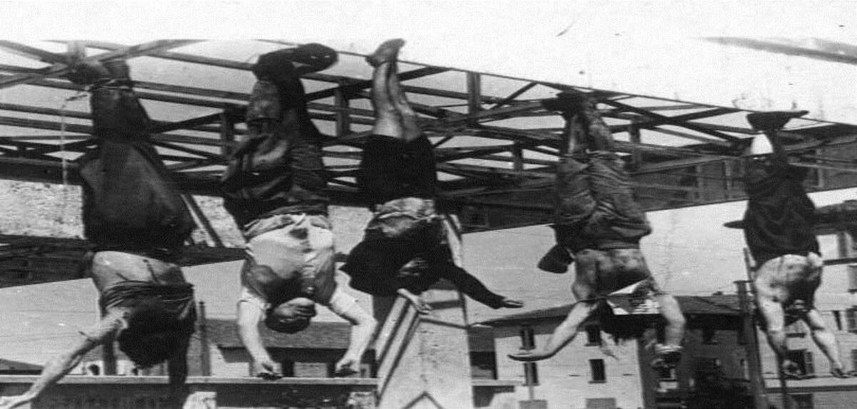 FILE - In this April 28, 1945 file photo, the bodies of some fascist leaders are hanged by their feet in downtown Milan's Piazzale Loreto, the day after the liberation of Milan. At center left, face to camera, is Benito Mussolini, who was killed the same day in Dongo, by the Como lake, while trying to escape, and whose body was taken to Milan to be exposed on the same square where the bodies of 15 resistance fighters were left as a warning to the population in August 1944. Italy on Saturday, April 25, 2015 celebrated the 70th anniversary of a partisan uprising against the Nazis and their Fascist allies at the end of World War II. President Sergio Mattarella marked Liberation Day by laying a wreath on the tomb of the unknown soldier in Rome. (AP Photo, File)