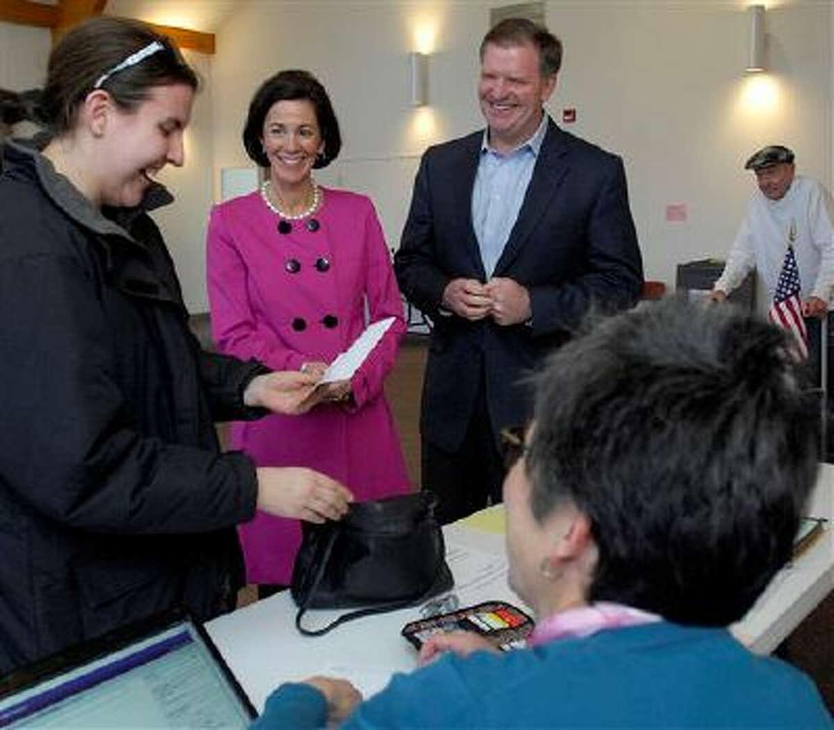State Senator Bill Brady and his wife Nancy talk with fellow voter Katie Graehling of Bloomington while checking in with election judge Karen Fleming for their ballots as they prepare to vote in the 2014 primary election Tuesday. (AP Photo/The Pantagraph, Lori Ann Cook-Neisler)