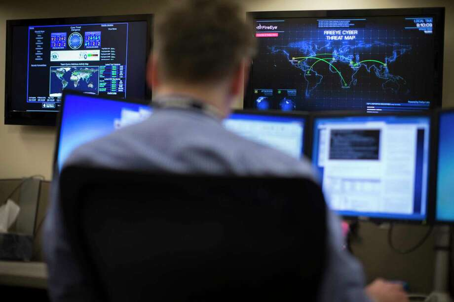 In this May 20, 2015 photo, security specialist Erik Dickmeyer works at a computer station with a cyber threat map displayed on a wall in front of him in the Cyber Security Operations Center at AEP headquarters in Columbus, Ohio. Photo: AP Photo/John Minchillo  / AP