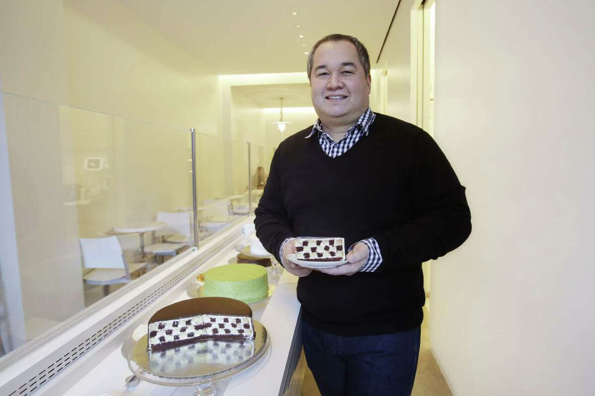 In this Dec. 17, 2014 photo, Ken Romaniszyn, owner of Lady M Cake Boutique, poses for a photo while holding a slice of his Checkers cake, at one of his New York shops.