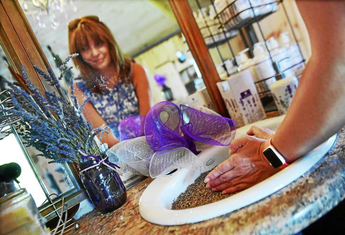 Denise Salafia shapes lavender seeds into a heart in the gift shop.