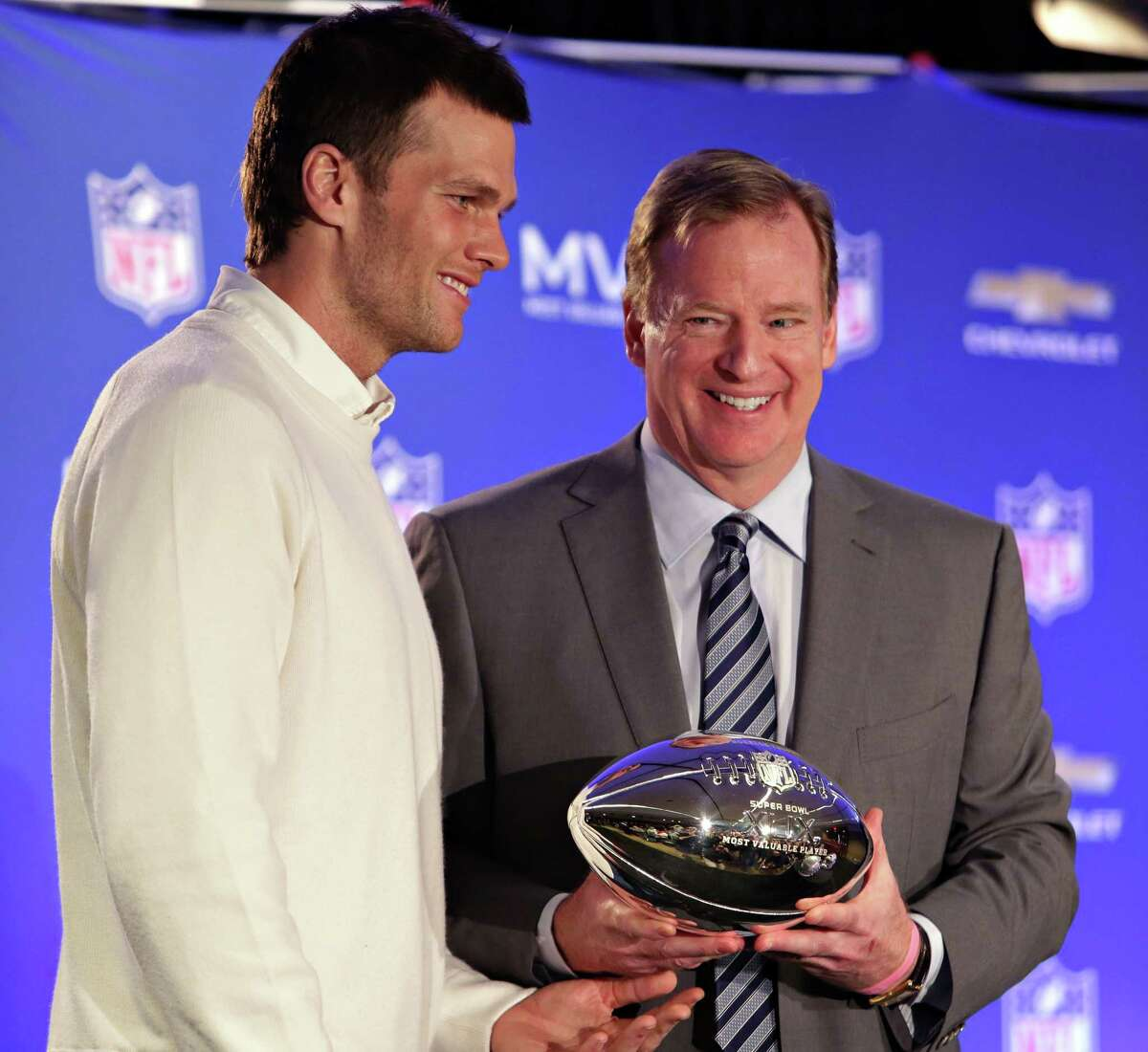 In this Feb. 2, 2015 photo, New England Patriots quarterback Tom Brady, left, poses with NFL Commissioner Rodger Goodell during a news conference where Goodell presented Brady with the MVP award from the NFL Super Bowl XLIX football game.