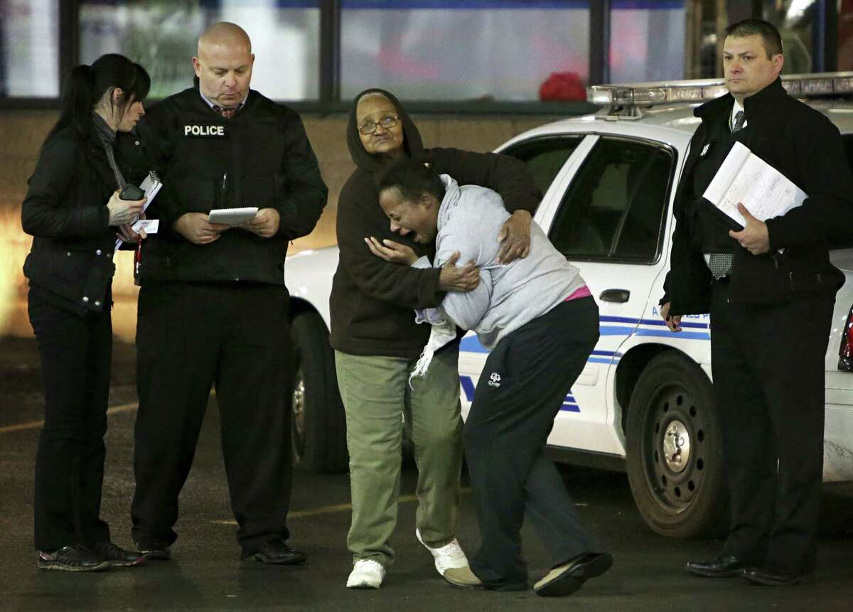 Toni Martin, front center, cries out on Dec. 24, 2014 as she talks to police at the scene where she says her son was fatally shot Tuesday at a gas station in Berkeley, Mo. Authorities did not immediately identify the man who was shot. But the St. Louis Post-Dispatch reported that Toni Martin, said he was her son, Antonio Martin.