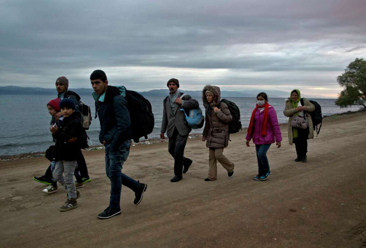 In this Thursday, Dec. 3, 2015, photo, Yazidi refugee Samir Qasu, 45, from Sinjar, Iraq, and his wife Bessi, 42, their two daughters Delphine, 18, Dunia 13, and their two sons Dilshad, 17, and Dildar, 10, walk toward a gathering point to board a bus to a registration center, after arriving on a vessel from the Turkish coast to the northeastern Greek island of Lesbos. The Oasus, left the Turkish coast before dawn on Dec. 3 bound for the island of Lesbos, the first port of EU call for nearly 400,000 asylum seekers this year.