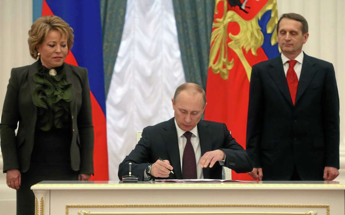 Russian President Vladimir Putin, flanked by Upper House Speaker Valentina Matviyenko, left, and Lower House Speaker Sergei Naryshkin, signs bills making Crimea part of Russia in the Kremlin in Moscow, Friday, March 21, 2014. President Vladimir Putin completed the annexation of Crimea on Friday, signing the peninsula into Russia at nearly the same time his Ukrainian counterpart sealed a deal pulling his country closer into Europe's orbit. (AP Photo/Sergei Chirikov, Pool)
