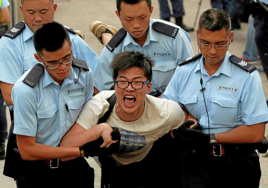 A protester, center, is taken away by police offices after hundreds of protesters stage a peaceful sit-ins overnight on a street in the financial district in Hong Kong Wednesday, July 2, 2014, following a huge rally to show their support for democratic reform and oppose Beijing's desire to have the final say on candidates for the chief executive's job. (AP Photo/Vincent Yu) Photo: AP / AP