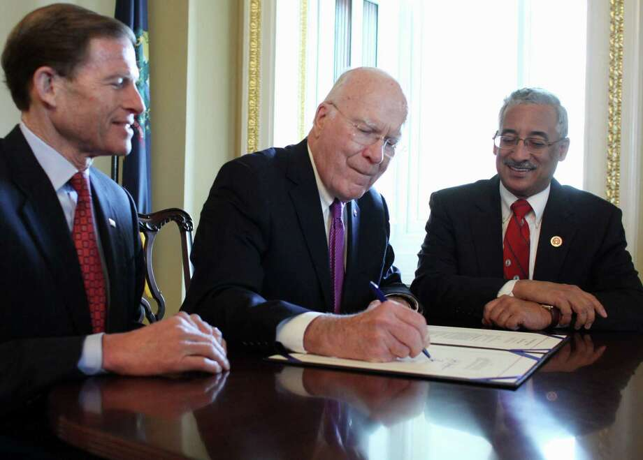 Senate Judiciary Committee Chairman Sen. Patrick Leahy, D-Vt., center, flanked by Senate Judiciary Committee member Sen. Richard Blumenthal, D-Conn., left, and House Judiciary Committee member Rep. Bobby Scott, D-Va., signs H.R. 1447, The Death in Custody Reporting Act, on Capitol Hill in Washington on Dec. 12, 2014, before sending it to President Barack Obama. Photo: AP Photo/Lauren Victoria Burke  / FR132934 AP