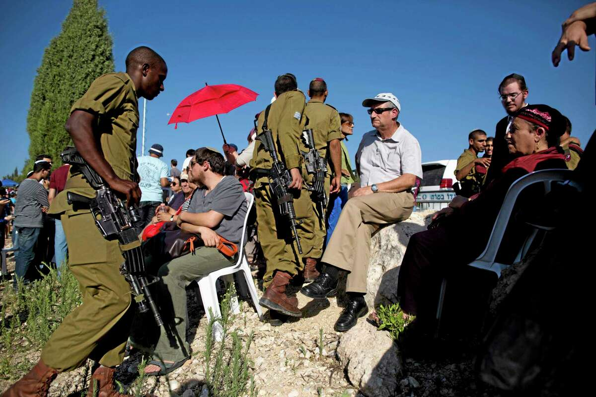 Israelis attend the funeral of three Israeli teenagers, Eyal Yifrah, 19, Gilad Shaar, 16, and Naftali Fraenkel, a 16-year-old with dual Israeli-American citizenship, in the Israeli town of Modiin on Tuesday, July 1, 2014. Tens of thousands of mourners converged Tuesday in central Israel for a funeral service for three teenagers found dead in the West Bank after a two week search and crackdown on the Hamas militant group, which Israeli leaders have accused of abducting and killing the young men.(AP Photo/Oded Balilty)