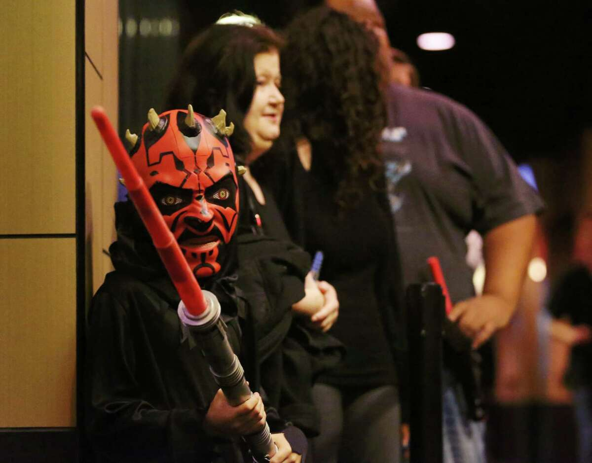 """Logan Gradney, 9, dressed as Darth Maul, waits in line with family members before a showing of the movie """"Star Wars: The Force Awakens"""" Thursday Dec. 17, 2015 in Houston. An 18-year-old Montana man is charged with threatening to shoot a boy for sharing information about a subplot of the new """"Star Wars"""" movie during an online conversation."""