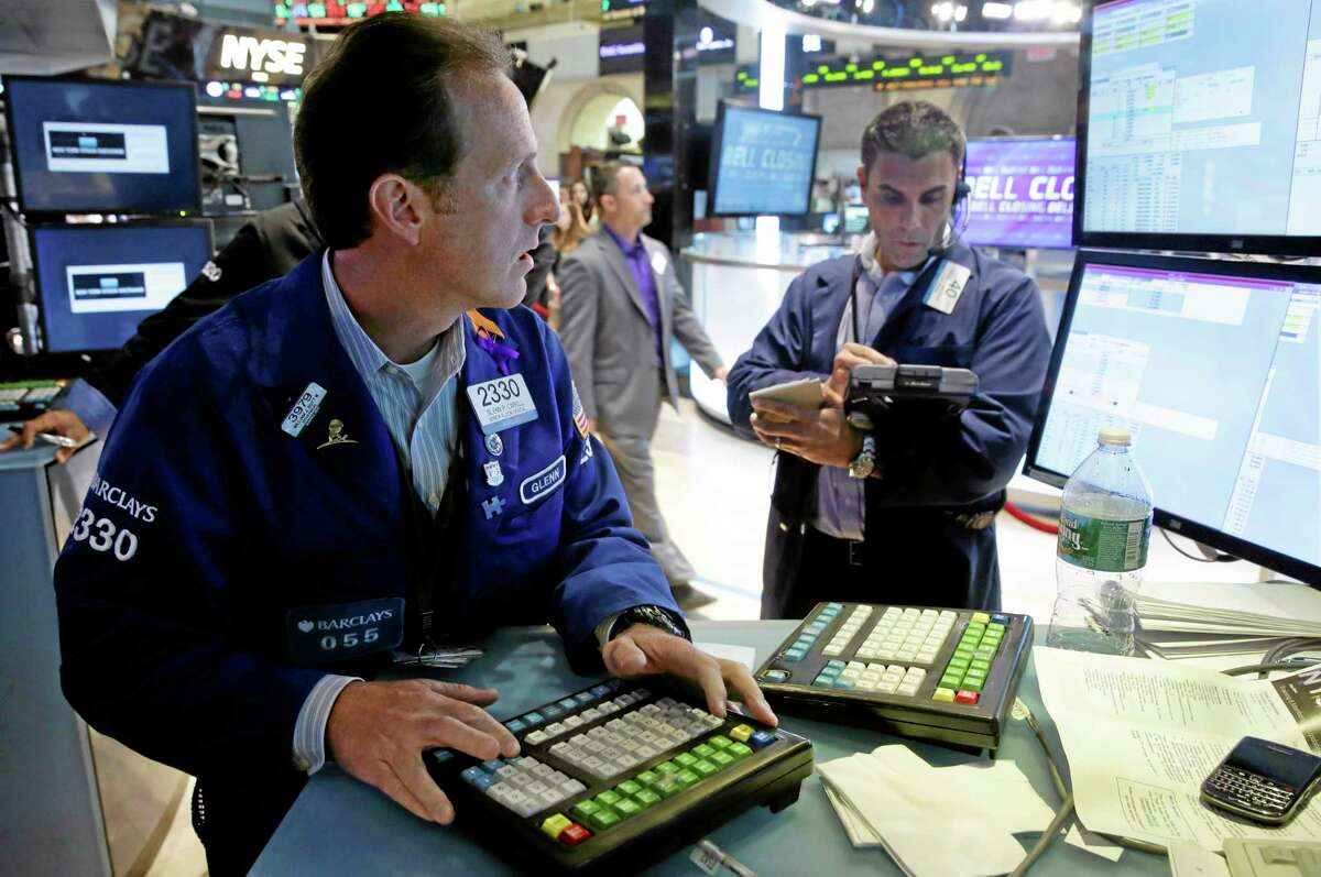 Specialist Glenn Carell, left, works at his post on the floor of the New York Stock Exchange Thursday.