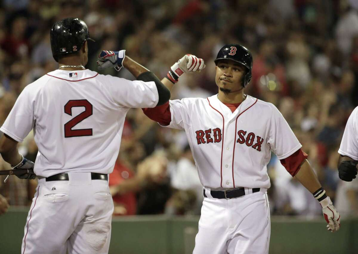 Mookie Betts, right, is welcomed home by Xander Bogaerts after hitting a two-run home run.