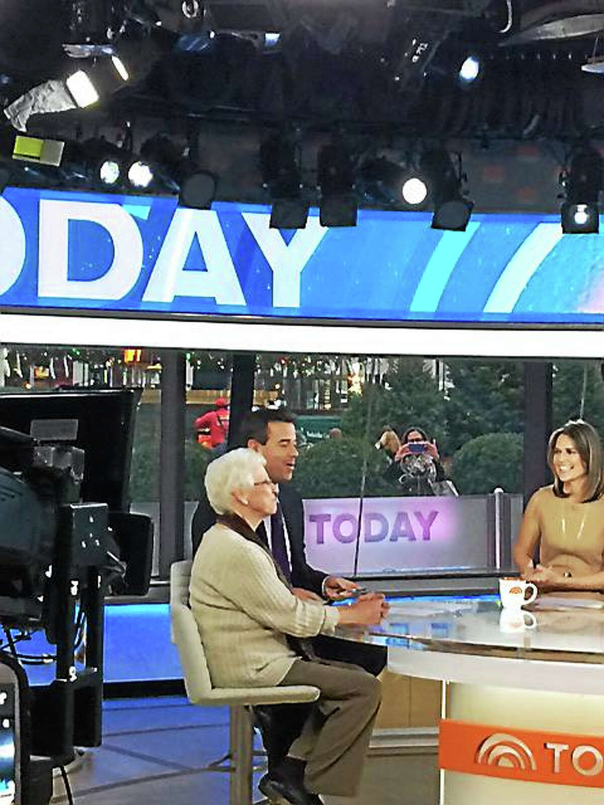 "Catherine Brutzman, 76, left, was the guest on the ""Today"" show's ""Pay It Forward"" segment, celebrating her commitment to work, family and community service. Carson Daly, center, chose her. Natalie Morales looks on at right."