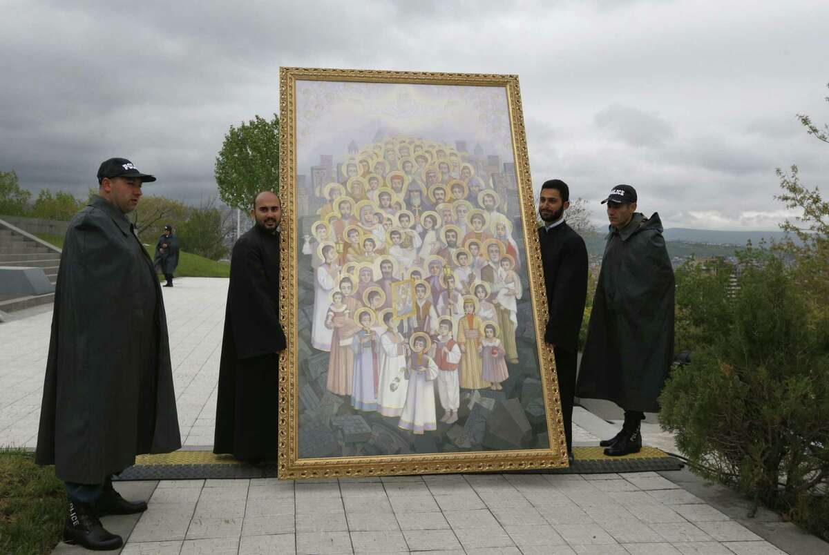 Armenian police officers and priests pose for a photograph next to an icon of canonized victims of massacres at memorial to Armenians killed by the Ottoman Turks, during a ceremony to mark the centenary of the mass killings, in Yerevan, Armenia, Friday, April 24, 2015. Armenians on Friday marked the centenary of what historians estimate to be the slaughter of up to 1.5 million Armenians by Ottoman Turks, an event widely viewed by scholars as genocide. Turkey, however, denies the deaths constituted genocide and says the death toll has been inflated. (AP Photo/Sergei Grits)