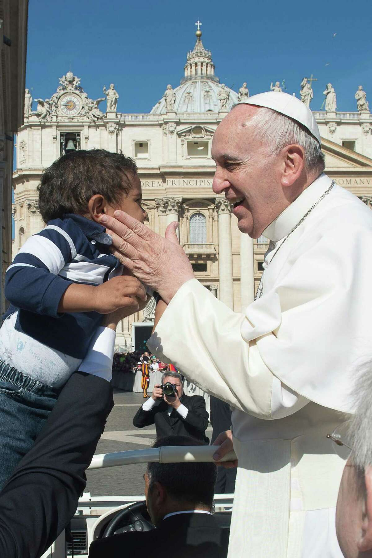 Pope Francis caresses a child as he arrives for his weekly general audience, in St. Peter's Square, at the Vatican, Wednesday, April 22, 2015. (LíOsservatore Romano/Pool Photo via AP)
