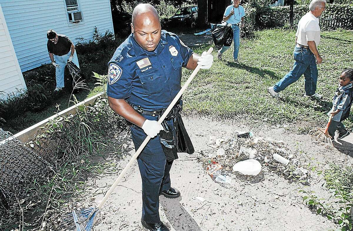 Middletown Police Officer Gary Wallace participates in the 2002 North End clean up along with property owners, residents and members of the North End Action Team in this archive photo. Residents are invited to help beautify the area on Saturday starting at Macdonough Elementary