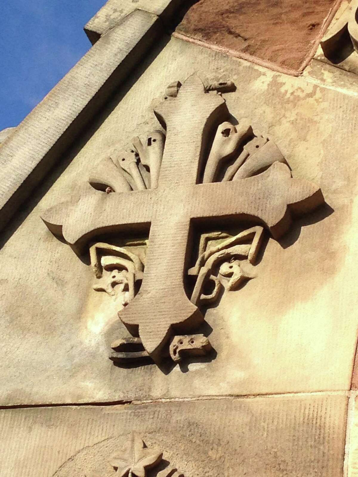 In this Dec. 17, 2014 photo, a detail of a revolver carved into the entrance of the Church of the Good Shepherd, which was built by the widow of Samuel Colt, is seen in Hartford, Conn.