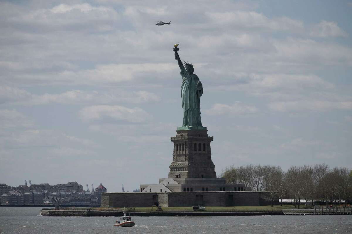 An NYPD helicopter flies over the Statue of Liberty as a coast guard boat patrols the waters, Friday, April 24, 2015, in New York. The Statue of Liberty was evacuated as a precaution on Friday after a bomb threat, forcing hundreds of tourists to be herded off the island.