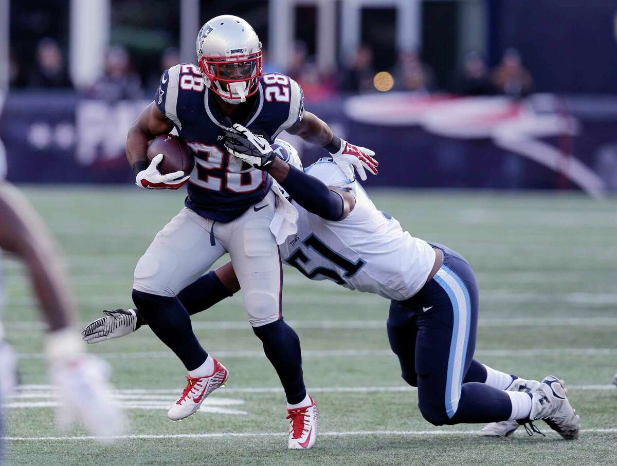 Patriots running back James White (28) runs from Titans linebacker David Bass in the first half Sunday.