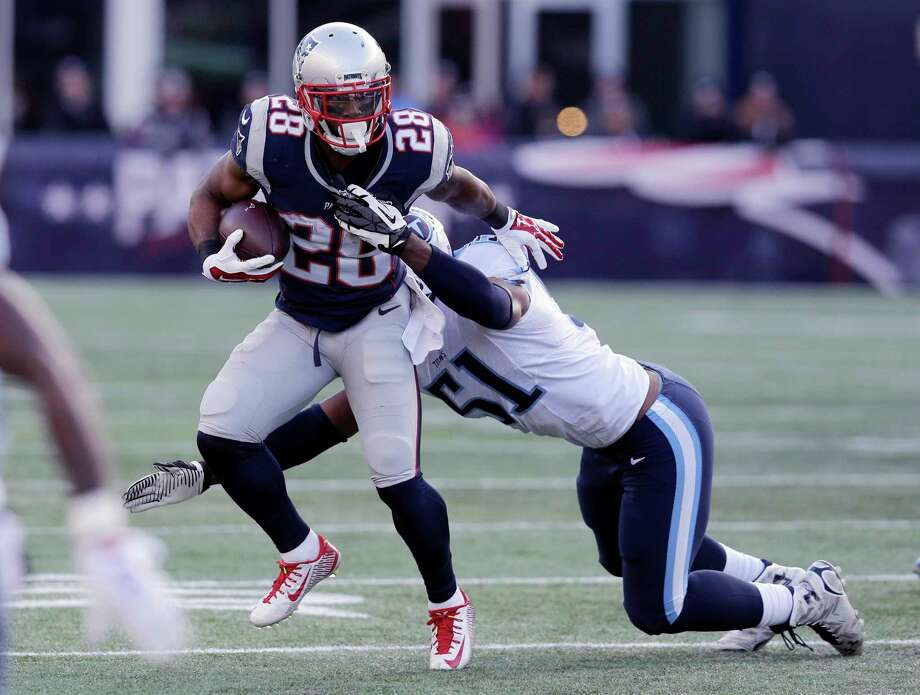 Patriots running back James White (28) runs from Titans linebacker David Bass in the first half Sunday. Photo: Charles Krupa — The Associated Press  / AP