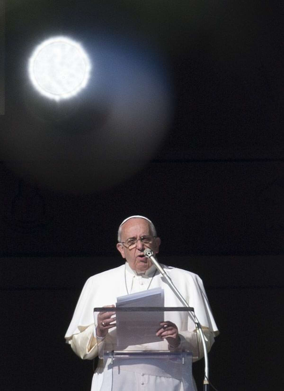 Pope Francis delivers his speech during the Angelus noon prayer he celebrated from the window of his studio overlooking St. Peter's Square at the Vatican, Sunday, Dec. 21, 2014. On top, left, is a Christmas tree's decoration reflecting sun light. (AP Photo/Alessandra Tarantino)