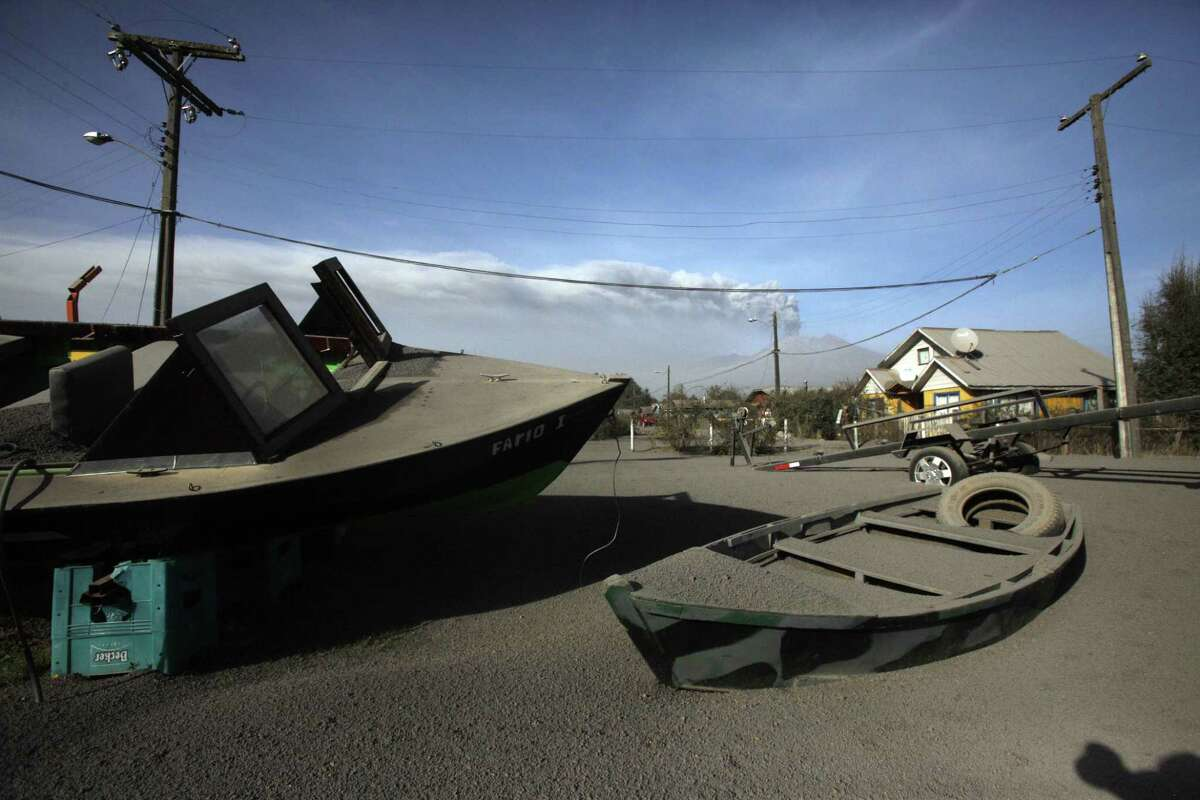 Boats dusted with volcanic ash deposited from the eruptions of the nearby Calbuco volcano, pictured in background, sit parked in front of a home in Puerto Varas, Chile, Friday, April 24, 2015. The volcano, which had been dormant for more than four decades, erupted Wednesday. The head of the National Mining and Geology Service said Friday that the volcano's eruptive process could last weeks and even months. (AP Photo/Luis Hidalgo)