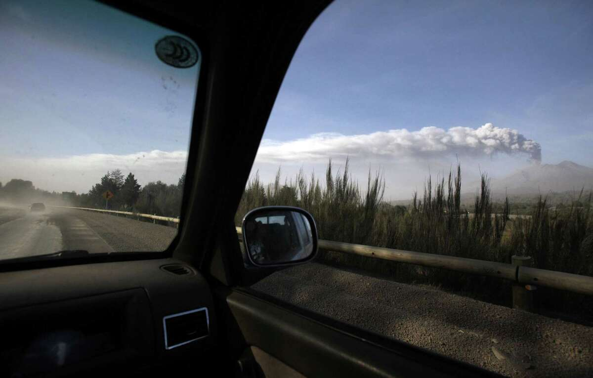 Plumes of smoke and ash billow from the Calbuco volcano as seen from the passenger seat of a car, in Puerto Varas, Chile, Friday, April 24, 2015. The volcano, which had been dormant for more than four decades, erupted Wednesday. The head of the National Mining and Geology Service said Friday that the volcano's eruptive process could last weeks and even months. (AP Photo/Luis Hidalgo)