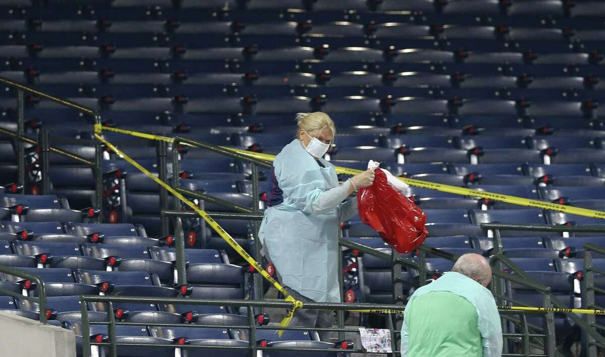 People clean a section of the lower seating area at Turner Field where a fan fell from the upper deck during a baseball game between the Atlanta Braves and the New York Yankees on Saturday, Aug. 29, 2015 in Atlanta. The fan was pronounce dead at Grady Memorial Hospital, authorities said.