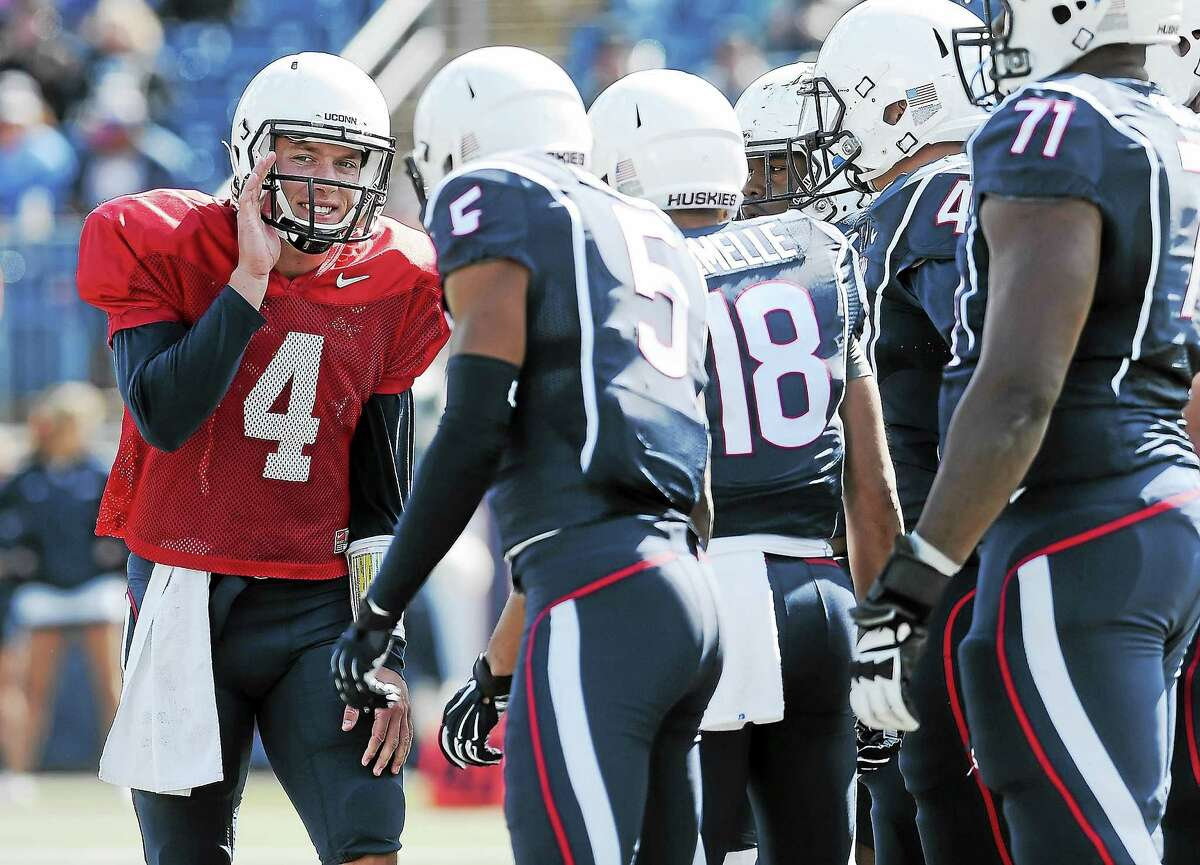UConn quarterback Bryant Shirreffs, left, talks with his team during the first half of UConn's Blue-White spring game at Rentschler Field in April.