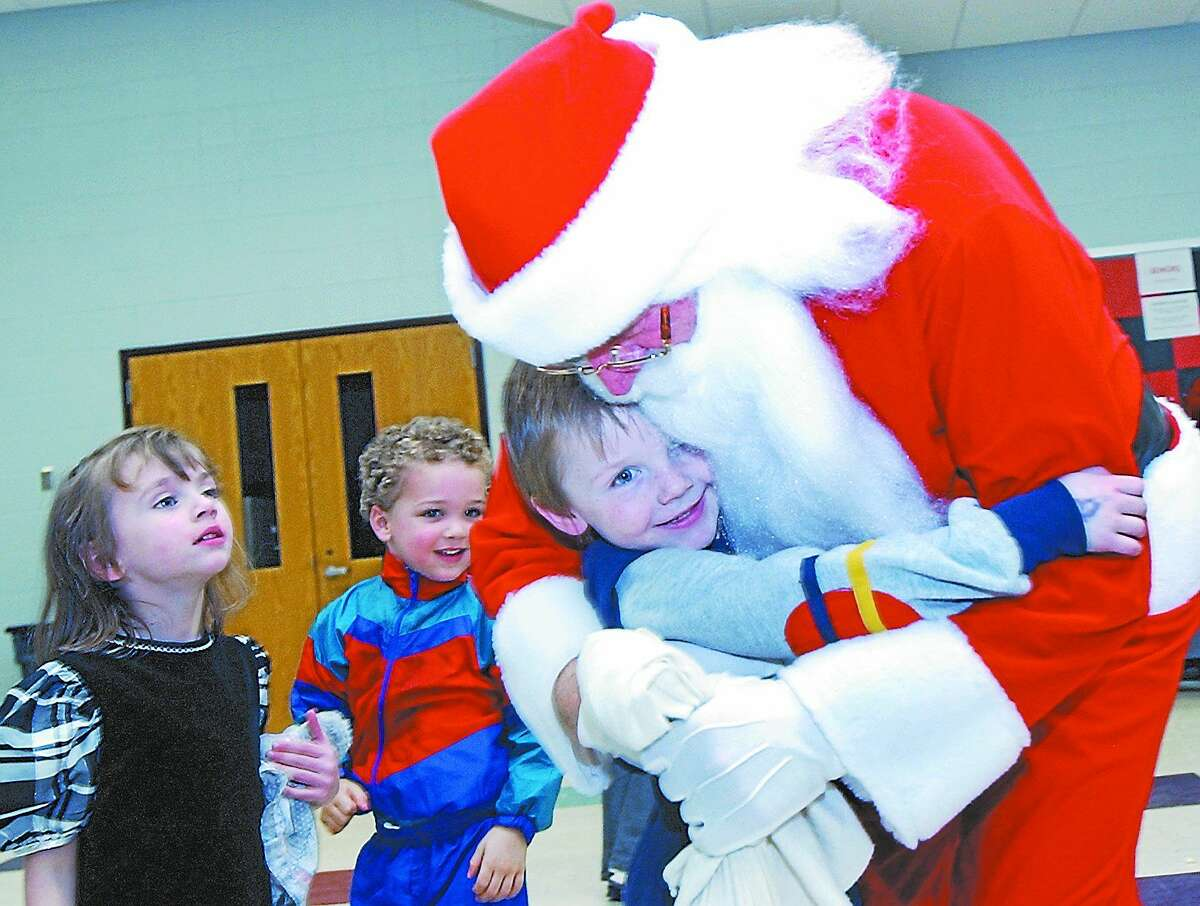 In this 2002 photo, Adam Michaud, 5, of Cromwell, hugs Santa Claus as Emma Vann and Trey Taylor, both 4 and from Cromwell, wait their turn during a holiday party for children at Cromwell High School.