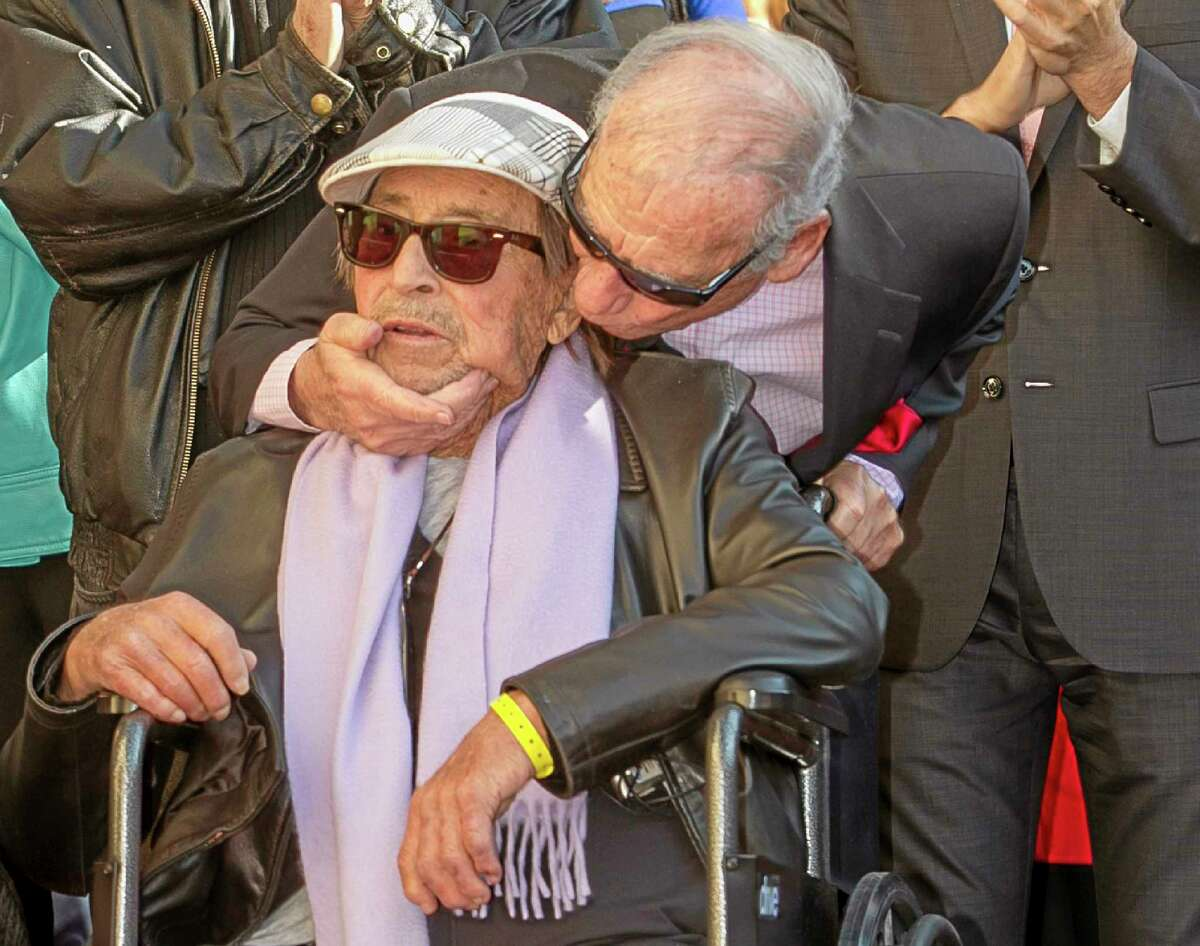 FILE - In this Friday, Dec. 13, 2013, file photo, actor Mel Brooks, right, kisses fellow actor director Paul Mazursky, as Mazursky is honored with a star on the Hollywood Walk of Fame in Los Angeles. Mazursky, the writer-director of such films as