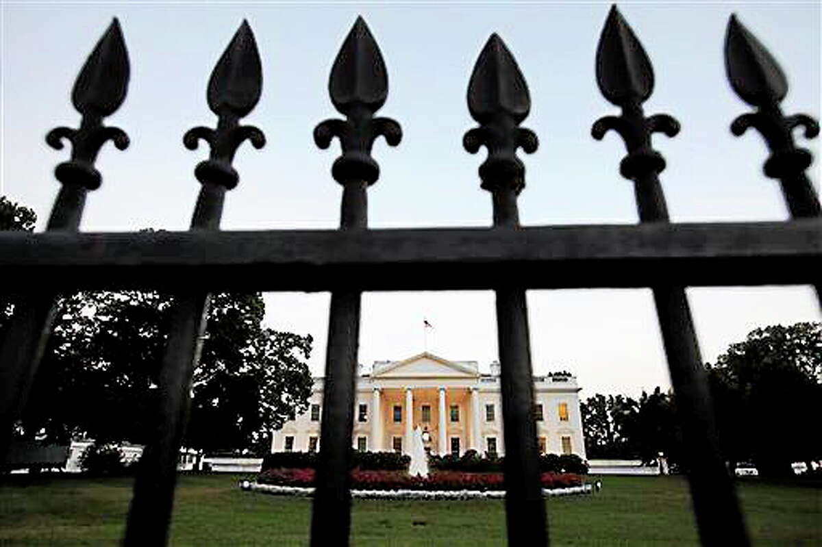 In this file photo, the White House is seen through a fence shortly before President Barack Obama delivered a speech in July, 2011.