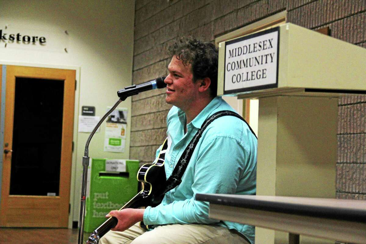 Middlesex Community College student Bejamin Gelfand offers a musical performance at Founder's Hall on the Middletown campus. Gelfand performed a couple of songs, and shared ideas on song writing techniques.