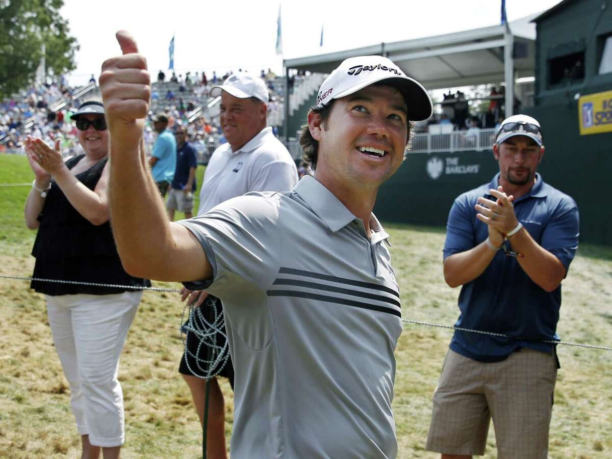 Brian Harman gives thumbs-up to a cheering gallery as he walks off the 18th hole after finishing with two holes-in-one in the final round of play at The Barclays on Sunday.