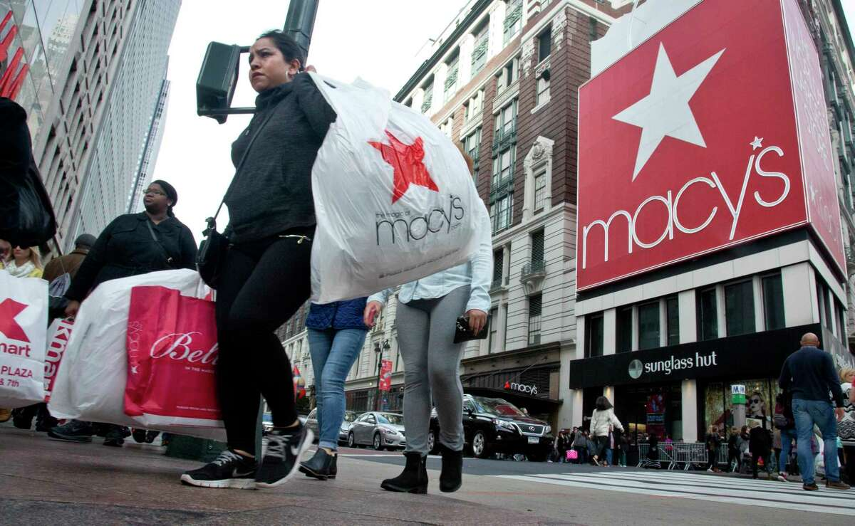 In this Nov. 27, 2015 photo, shoppers carry bags as they cross a pedestrian walkway near Macy's in Herald Square in New York.