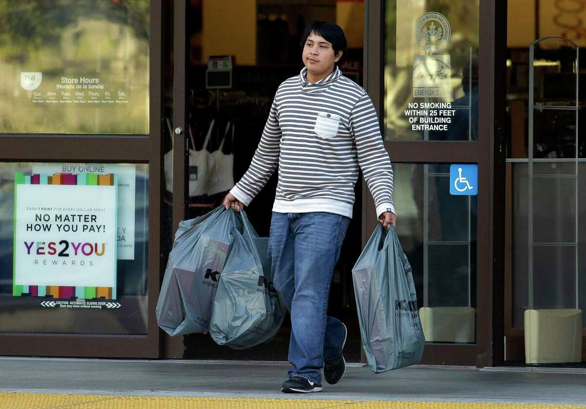A man carries bags out of a department store on Dec. 17, 2015 in Alameda, Calif.
